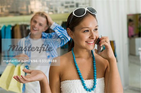 Woman Using Cell Phone in Clothing Boutique Stock Photo - Premium Royalty-Free, Image code: 694-03318488