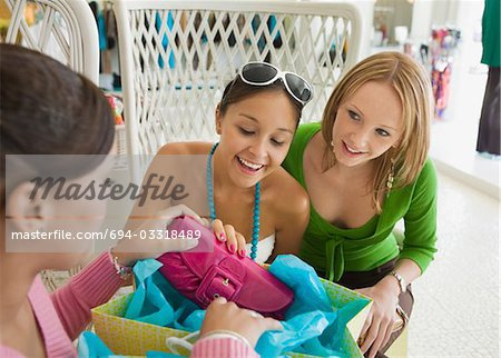 Friends Looking at Shopping Purchases Stock Photo - Premium Royalty-Free, Image code: 694-03318489
