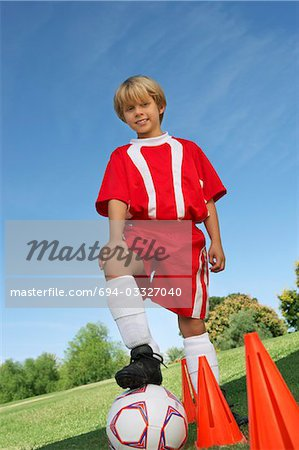 Boy (7-9 years) soccer player holding foot on ball, portrait Stock Photo - Premium Royalty-Free, Image code: 694-03327040