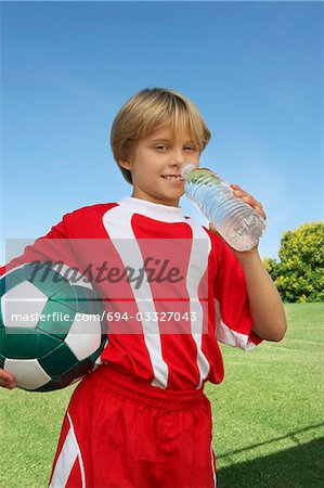 Boy (7-9 years) soccer player holding ball and water bottle, portrait Stock Photo - Premium Royalty-Free, Image code: 694-03327043