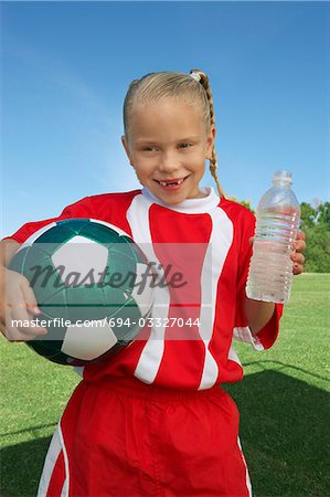 Girl (7-9 years) soccer player holding ball and water bottle, portrait Stock Photo - Premium Royalty-Free, Image code: 694-03327044