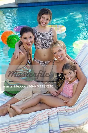 Mother, grandmother and two girls on deck chair by swimming pool, portrait Stock Photo - Premium Royalty-Free, Image code: 694-03327230