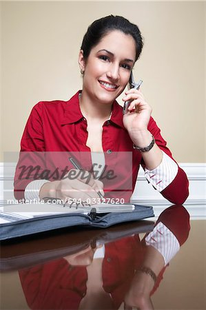 Business woman using mobile phone and writing in diary in office, portrait Stock Photo - Premium Royalty-Free, Image code: 694-03327620