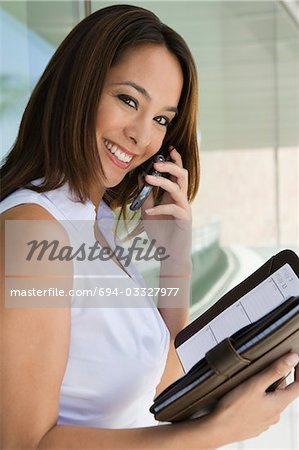 Woman using cell phone holding planner, portrait Stock Photo - Premium Royalty-Free, Image code: 694-03327977