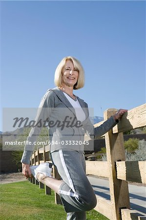 Mature woman stretches leg in warm up exercise Stock Photo - Premium Royalty-Free, Image code: 694-03332045