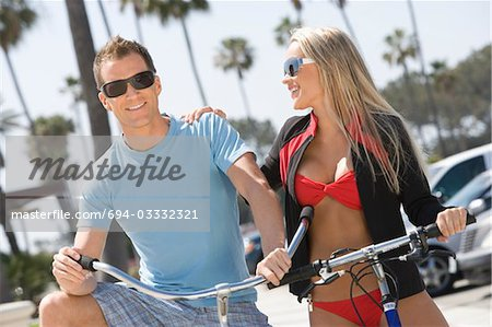 Couple on bikes at the beach Stock Photo - Premium Royalty-Free, Image code: 694-03332321