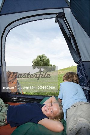 Brother and sister lie in a tent Stock Photo - Premium Royalty-Free, Image code: 694-03440989