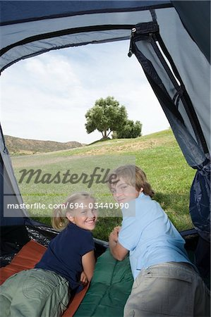 Brother and sister lie in a tent, looking back over their shoulders Stock Photo - Premium Royalty-Free, Image code: 694-03440990