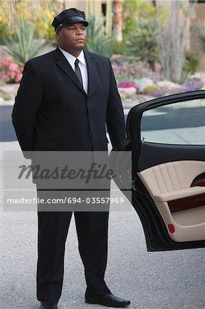 Chauffeur stands at open car door of luxury vehicle