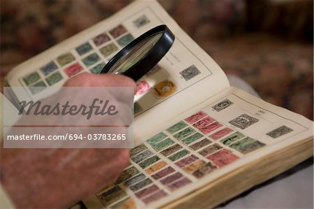 Senior man looks at stamp collection with magnifying glass Stock Photo - Premium Royalty-Free, Image code: 694-03783265