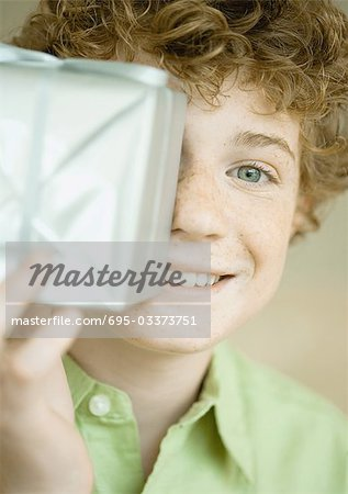 Boy holding up present in front of face Stock Photo - Premium Royalty-Free, Image code: 695-03373751