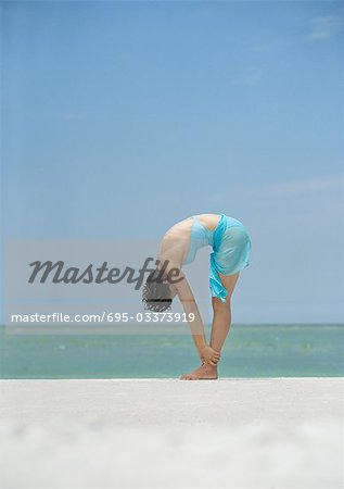 Woman bending over, holding ankles, on beach Stock Photo - Premium Royalty-Free, Image code: 695-03373919