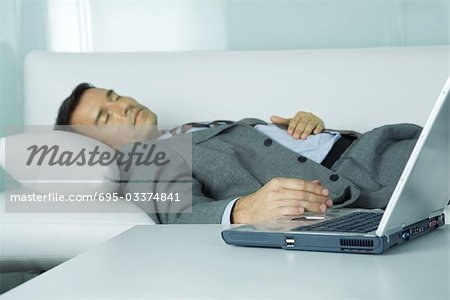 Businessman sleeping on sofa, hand resting on laptop Stock Photo - Premium Royalty-Free, Image code: 695-03374841