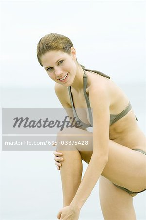 Young woman in bikini standing with one knee up, touching leg, smiling at camera Stock Photo - Premium Royalty-Free, Image code: 695-03375428