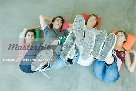 Four teen friends lying on backs on floor, holding up legs, focus on soles of shoes Stock Photo - Premium Royalty-Free, Image code: 695-03375664