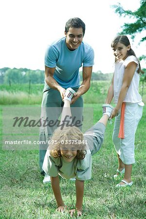 Family outdoors, father and sister holding boy's legs like wheelbarrow Stock Photo - Premium Royalty-Free, Image code: 695-03375841