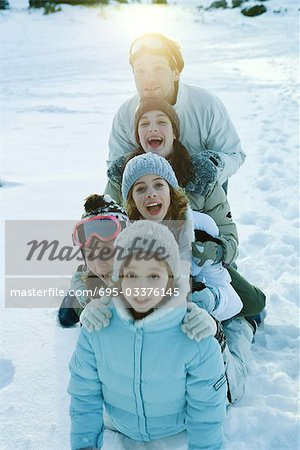 Group kneeling in snow, lined up one behind the other, smiling and laughing Stock Photo - Premium Royalty-Free, Image code: 695-03376145