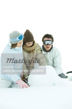Three young friends crouching in snow, making snowball, one looking at camera Stock Photo - Premium Royalty-Free, Image code: 695-03376299