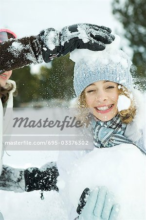 Teenage girl being hit with snowballs, smiling at camera Stock Photo - Premium Royalty-Free, Image code: 695-03376302