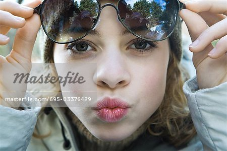 Preteen girl lifting sunglasses, puckering at camera, close-up Stock Photo - Premium Royalty-Free, Image code: 695-03376429