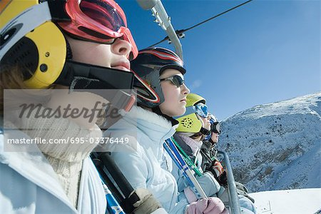 Four young skiers on chair lift, looking away, side view Stock Photo - Premium Royalty-Free, Image code: 695-03376449