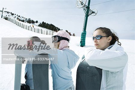 Young friends standing together, holding snowboards, looking away Stock Photo - Premium Royalty-Free, Image code: 695-03376487