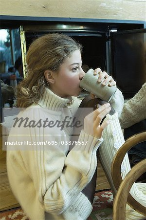 Teen girl drinking hot beverage by fireplace Stock Photo - Premium Royalty-Free, Image code: 695-03376557