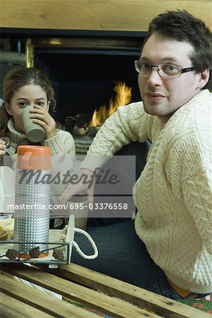 Young man and teen girl drinking hot drinks by fire place Stock Photo - Premium Royalty-Free, Image code: 695-03376558