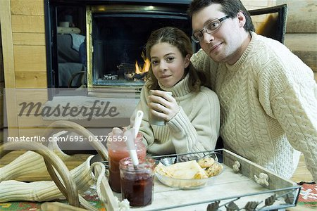 Young man and teen girl drinking hot drinks by fire place Stock Photo - Premium Royalty-Free, Image code: 695-03376559