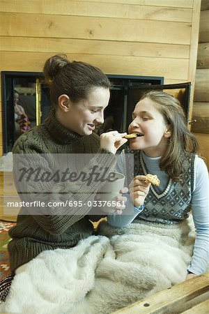 Teen girls having snack by fire place Stock Photo - Premium Royalty-Free, Image code: 695-03376561