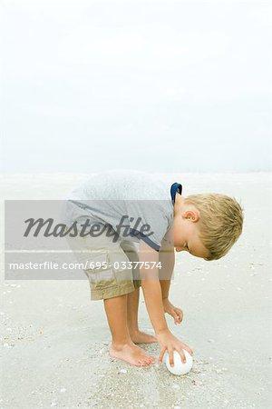 Little boy bending over to pick up ball on beach, full length