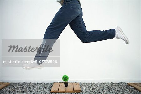Man jumping in the air over bonsai, side view, cropped Stock Photo - Premium Royalty-Free, Image code: 695-03378506