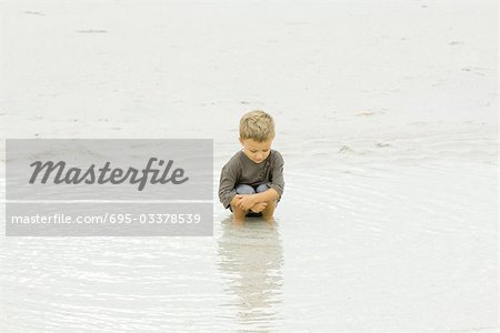 Little boy crouching in water at the beach, looking down Stock Photo - Premium Royalty-Free, Image code: 695-03378539