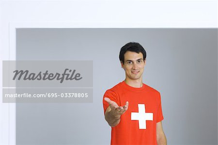 Young man wearing tee-shirt with plus symbol, holding out hand, smiling at camera Stock Photo - Premium Royalty-Free, Image code: 695-03378805