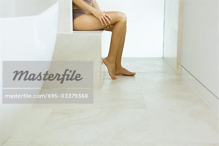 Woman sitting in bathroom, in underwear, low section Stock Photo - Premium Royalty-Free, Image code: 695-03379368
