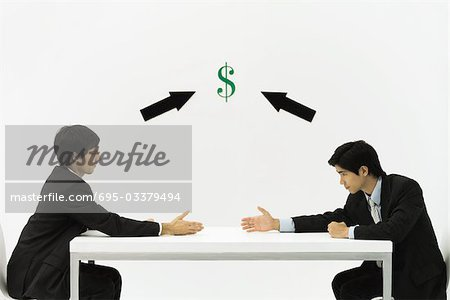 Two businessmen face to face, reaching to shake hands, dollar sign and arrows between them Stock Photo - Premium Royalty-Free, Image code: 695-03379494