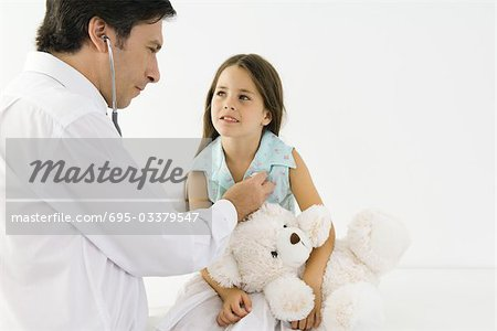 Pediatrician listening to girl's heart with stethoscope, girl holding teddy bear Stock Photo - Premium Royalty-Free, Image code: 695-03379547