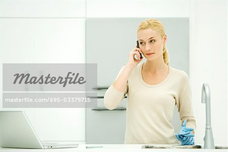 Young woman standing in kitchen, holding rubber gloves, using cell phone Stock Photo - Premium Royalty-Free, Image code: 695-03379715