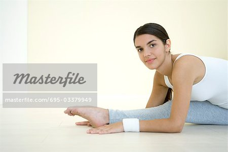 Woman doing split, smiling at camera Stock Photo - Premium Royalty-Free, Image code: 695-03379949