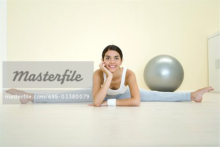 Young woman doing split on the ground, smiling at camera Stock Photo - Premium Royalty-Free, Image code: 695-03380079