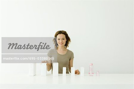 Woman with milk cartons and baby bottle, smiling at camera Stock Photo - Premium Royalty-Free, Image code: 695-03380145