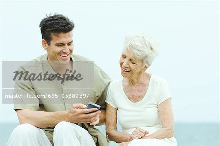 Senior woman with adult son looking at his wireless device Stock Photo - Premium Royalty-Free, Image code: 695-03380397