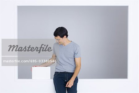 Man sitting on ledge, touching box, smiling Stock Photo - Premium Royalty-Free, Image code: 695-03380546