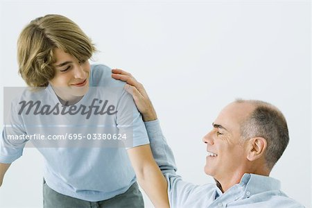 Man sitting with hand on teen son's shoulder, both smiling Stock Photo - Premium Royalty-Free, Image code: 695-03380624