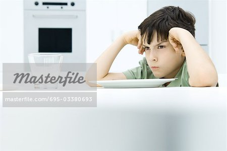 Boy sitting at dinner table, holding head, sulking Stock Photo - Premium Royalty-Free, Image code: 695-03380693