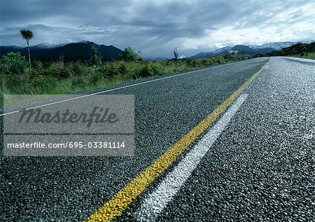 New Zealand, wet road, stormy weather in distance Stock Photo - Premium Royalty-Free, Image code: 695-03381114