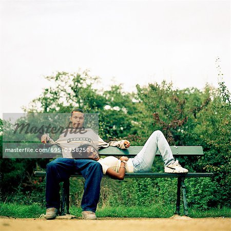 Young woman resting head on young man's lap, on bench outside
