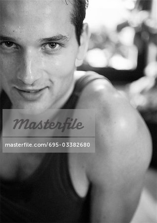 Man wearing tanktop, looking at camera, partial view, close-up, black and white. Stock Photo - Premium Royalty-Free, Image code: 695-03382680