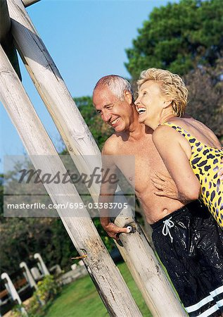Mature man and woman standing in bathing suits in outdoor shower Stock Photo - Premium Royalty-Free, Image code: 695-03383705