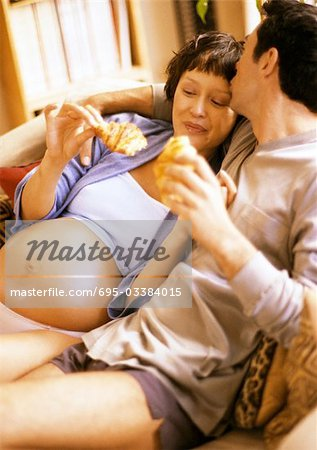 Man on sofa kissing pregnant woman, both holding croissants Stock Photo - Premium Royalty-Free, Image code: 695-03384015
